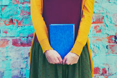 Girl holding book in hands Stock Photos