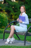 Girl holding book on her chest sitting in the park Royalty Free Stock Image