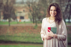 Girl holding book in park Royalty Free Stock Photos
