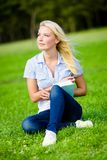 Girl holding book sits on the grass Stock Photography