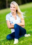 Girl holding book sits on the green grass Stock Photos