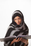 Girl holding book. A girl wearing a black hijab holding a book isolated on a white background Stock Photo