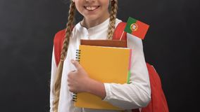 Girl holding books with Portuguese flag and smiling at camera, language studying. Stock footage stock footage
