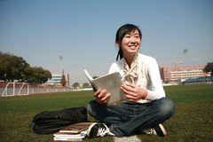 Girl holding books sitting on grasslan Royalty Free Stock Images