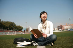 Girl holding books sitting on grasslan Royalty Free Stock Image