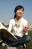 Girl holding books sitting on grasslan Royalty Free Stock Photo