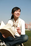 Girl holding books sitting on grasslan Stock Image