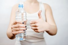Girl holding bottle of water in her hand stock photography
