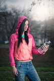 Girl holding bottle of water in park Stock Images