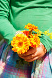 Girl holding a bouquet of orange flowers.  royalty free stock images