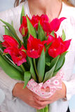 Girl holding a bouquet of red tulips Stock Photo