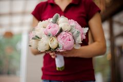 Girl holding bouquet of rose and champagne color peonies. Girl in red shirt holding in her hands bouquet of pink and champagne color tender peonies royalty free stock photography
