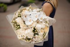 Girl holding bouquet of white and champagne color flowers. Girl in the blue dress holding in her hands a beautiful bouquet of white and champagne color flowers stock photography