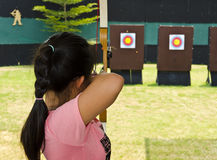 The girl holding the bow. Girl aiming with a bow and arrow Royalty Free Stock Photo