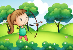 A girl holding a bow and arrow in the hills Stock Images