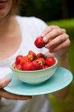 Girl holding a bowl of strawberries Stock Photography