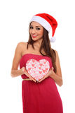 Girl holding a box. Girl with dress and santa claus hat holding a heart shape box Royalty Free Stock Image