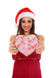 Girl holding a box. Girl with dress and santa claus hat holding a heart shape box Royalty Free Stock Images
