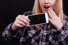 A girl is holding a broken smartphone in hand and screaming indignantly. Close-up. A young girl, of European appearance, is holding a modern broken smartphone Stock Photography