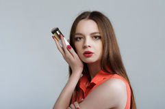 Girl holding a brush for blush in her hand, pressing it to his c Royalty Free Stock Photos