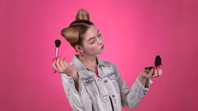 Girl holding a brush in her hand and powdering her face. Pink background stock footage