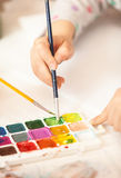 Girl holding brush and painting with watercolor Royalty Free Stock Photo