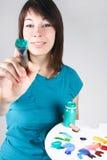 Girl holding brush and palette, making stroke Stock Images