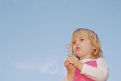 Girl holding bubble wand in two hands Royalty Free Stock Images