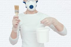 The girl is holding a bucket of paint and a brush for painting. royalty free stock photography