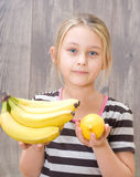 Girl holding a bunch of bananas and lemon Stock Photo