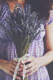 Girl holding bunch of dried lavender with lace ribbon and bow Stock Photo