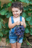 Girl holding bunch of grapes Stock Images