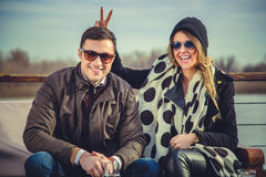 Girl holding bunny ears to her boyfriend. With river in background Stock Image