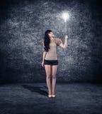 Girl holding a burning light bulb Stock Photo