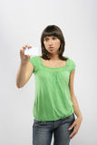 Girl holding a business card. Beautiful casual girl holding a business card Royalty Free Stock Image