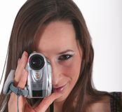 Girl holding camera. Woman holding and looking into a video camera Royalty Free Stock Image