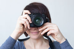 A girl is holding a camera by her face. Royalty Free Stock Image