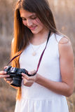 Girl holding a camera looking down Stock Photography