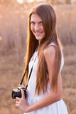 Girl holding a camera. Outdoors setting stock photography