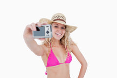 Girl holding a camera while photographing hers. Beautiful teenager photographing herself with her camera against a white background Royalty Free Stock Images