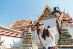 Girl holding camera and taking picture selfie. Pretty leisurely girl holding camera and taking picture selfie with wat pho temple in Bangkok, Thailand travel at Royalty Free Stock Images