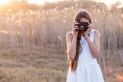 Girl holding a camera taking pictures. From the front royalty free stock photos