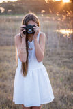 Girl holding a camera taking pictures. From the front stock photography