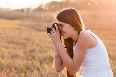 Girl holding a camera taking pictures. From the side royalty free stock photos