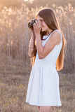 Girl holding a camera taking pictures. From the side stock photo