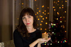 Girl holding a candle near a Christmas tree. Royalty Free Stock Photo