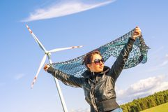 Girl holding canvas-cape and windturbine in background Royalty Free Stock Image