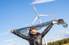 Girl holding canvas-cape and windturbine in background Royalty Free Stock Photo