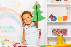 Girl holding carton Xmas tree standing at table Royalty Free Stock Image