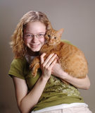 Girl holding cat. Portrait of a girl holding an orange cat Royalty Free Stock Photography